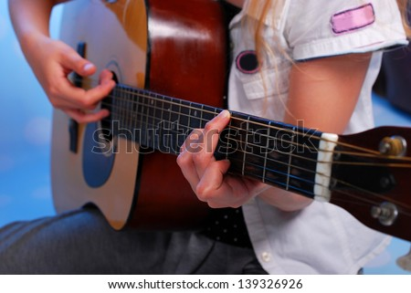 close up on the fingers of young girl playing acoustic guitar on the stage