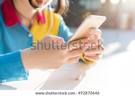 Close up on the hand of young woman holding a smart phone, tapping the screen - technology, social network, communication concept