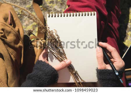 Close-up on the hands of a girl holding a blank notebook. A dry bouquet of herbs in her hand and a pencil. Travel designer artist #1098459023