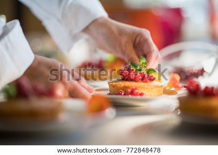 Close-up on the hands of the pastry chef decorating a cake with red currants and a mint leaf before serving.