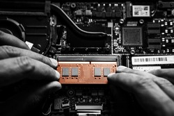 Close-up on the orange RAM memory that the hands of the service technician insert into the slot on the laptop computer.