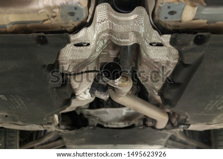 Close-up on the part of the bottom of the car from the front of the exhaust pipe and the catalyst disassembled during the repair in the workshop auto service vehicles #1495623926