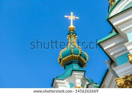 Close up on the tower of St Andrew's Church, Kiev, Ukraine. The church is small and painted blue and white with many decorations on it's facade. Picture taken from under the church. Clear and blue sky