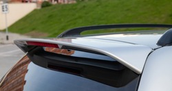 Close-up on the trunk lid of a gray car with a plastic spoiler over the rear window to improve the aerodynamics of the car body during tuning for racing.