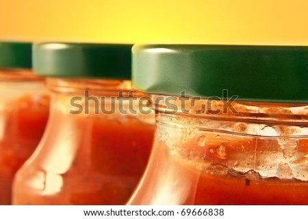 Close up on three pasta sauce jars with yellow background. Focus on foreground jar.