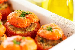Close-up on Traditional Provencal French stuffed tomatoes with meat, bread crumbs, rosemary, thyme, parsley and olive oil in a white ceramic dish aside a bottle of olive oil.