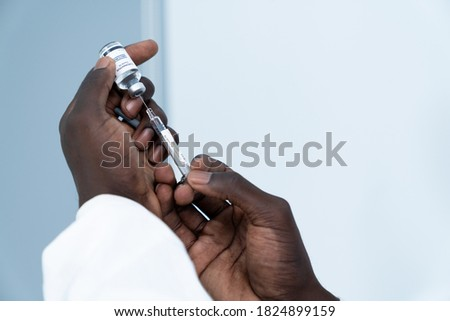Close up on Vaccine. Hand of African American scientist in laboratory holding a syringe and vial of coronavirus vaccine. The success of Virologists who invented the vaccine for Covid-19.
