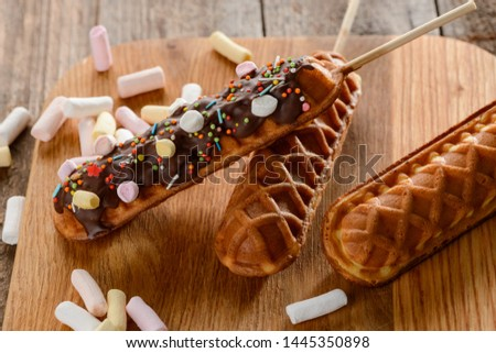 Close-up on waffle lollies. Wonderful desserts on a stick, being decorated with chocolate, marshmallow and sprinkles. Confectionery art.