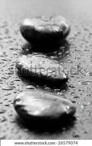 Close up on wet spa stones on dark wooden surface - stock photo
