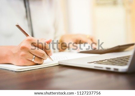 close up on woman hand writing on notebook and pressing on calculator for calculating cost estimating , senior accountant job working concept