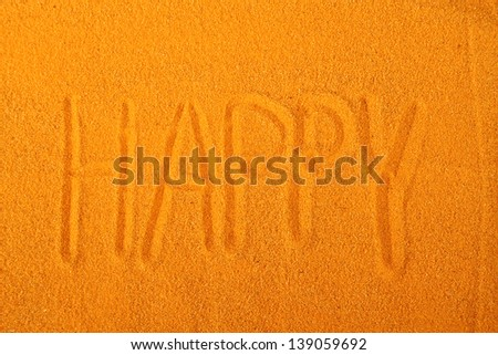 "Close-up on yellow sand written ""Happy"""