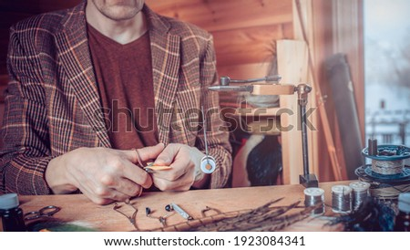 Close up on young man's hands tying a fly for fishing Stock fotó ©
