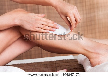 Close-up on young woman doing depilation on legs