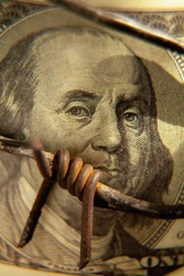 Close up one huundred US Dollar bill wrapped in barbed wire as symbol of economic warfare, sanctions and embargo busting.  Vertical image.