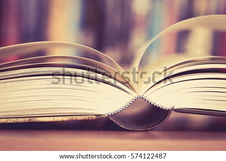 Close up opened book page with blurry bookshelf background for education and publication concept , extremely DOF with vintage retro color tone