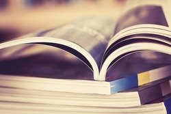 Close up opened magazine page with  blurry bookshelf background for publication concept , extremely DOF with vintage retro color tone