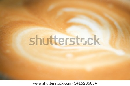 Close up or macro photo of a cup cappuccino coffee art floating on top. Royalty high-quality free stock photo image a cup of cappuccino coffee foam art with romantic heart shape from milk surface