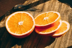 Close-up orange slices on a wooden cutting board in the kitchen  in the sun with a sharp contrast of light and shadows in bright lively and warm colors.