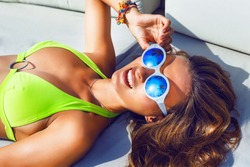 Close up outdoor fashion portrait of young woman with perfect bronze tanned skin, laying and herring sunbathe, wearing bright bikini and blue mirrored sunglasses with reflection of palms on it.