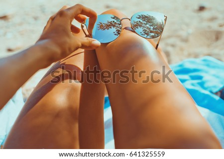 Close-up outdoor photo of sensual tanned female legs with fashionable sunglasses #641325559