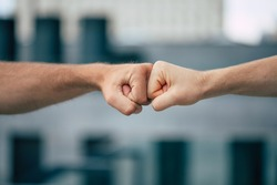 Close up outdoor photo of two men's fists holding together