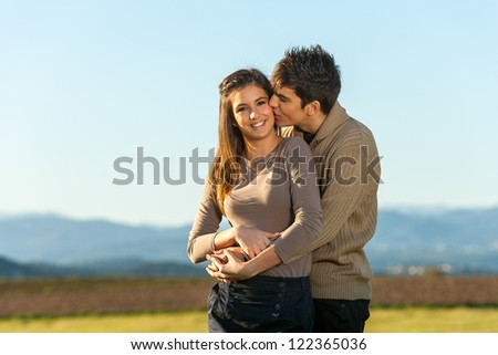 Close up outdoor portrait of boy showing girlfriend something in the distance.