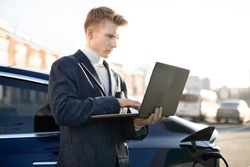 Close up outdoor portrait of concentrated purposeful likable young businessman, typing a message on laptop pc, while standing near his modern luxury electric car at urban charging station