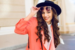 Close up  outdoor portrait of fashionable pretty woman   in casual bright spring or summer outfit , looking at camera, laughing.  Brunette  curly hairstyle. Bright sunny colors.