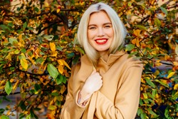 Close up outdoor portrait of young blond happy smiling woman with lips wearing flesh-coloured coat posing near autumn tree. Model with red lips, long blond hair. Lady looking at camera