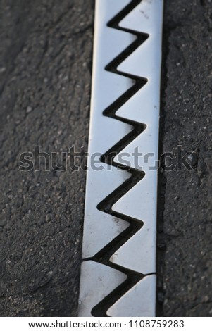Close up outdoor view from above of an iron dilatation joint placed on a bridge road. Zigzag line drawn of an bright steel surface. Abstract design with grey geometric shapes on the asphalt ground.   #1108759283