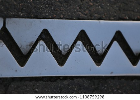 Close up outdoor view from above of an iron dilatation joint placed on a bridge road. Zigzag line drawn of an bright steel surface. Abstract design with grey geometric shapes on the asphalt ground.   #1108759298
