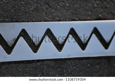 Close up outdoor view from above of an iron dilatation joint placed on a bridge road. Zigzag line drawn of an bright steel surface. Abstract design with grey geometric shapes on the asphalt ground.   #1108759304