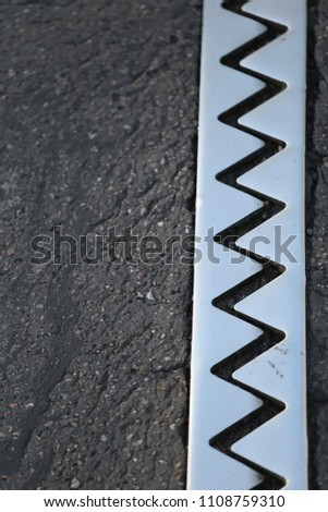 Close up outdoor view from above of an iron dilatation joint placed on a bridge road. Zigzag line drawn of an bright steel surface. Abstract design with grey geometric shapes on the asphalt ground.   #1108759310