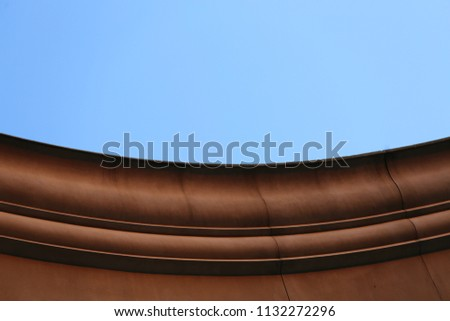 Close up outdoor view from bellow of the curving border of a stone roof. Isolated part of an ancient building made of blocks. Curved lines with a blue sky in background. Abstract architectural image. #1132272296