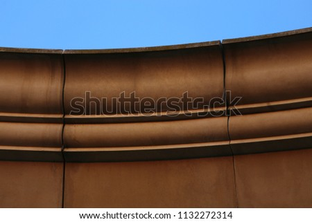Close up outdoor view from bellow of the curving border of a stone roof. Isolated part of an ancient building made of blocks. Curved lines with a blue sky in background. Abstract architectural image. #1132272314