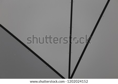 Close up outdoor view of part of a grey modern wall covered by metallic polygonal sheets. Abstract design with black lines and gray triangles. Futuristic geometric picture of a bright surface.