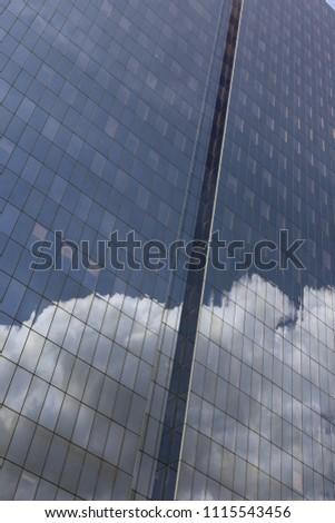 Close up outdoor view of part of a skyscraper with pattern of reflective glass windows. Blue cloudy sky reflected on the bright surface. Modern architecture with a big white cloud on the facade.  #1115543456
