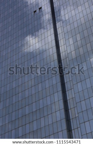 Close up outdoor view of part of a skyscraper with pattern of reflective glass windows. Blue cloudy sky reflected on the bright surface. Modern architecture with a big white cloud on the facade.  #1115543471