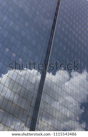Close up outdoor view of part of a skyscraper with pattern of reflective glass windows. Blue cloudy sky reflected on the bright surface. Modern architecture with a big white cloud on the facade.  #1115543486