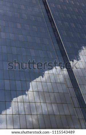 Close up outdoor view of part of a skyscraper with pattern of reflective glass windows. Blue cloudy sky reflected on the bright surface. Modern architecture with a big white cloud on the facade.  #1115543489