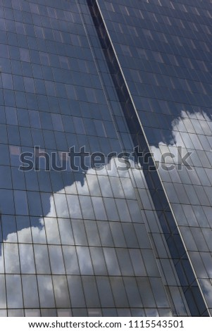 Close up outdoor view of part of a skyscraper with pattern of reflective glass windows. Blue cloudy sky reflected on the bright surface. Modern architecture with a big white cloud on the facade.  #1115543501