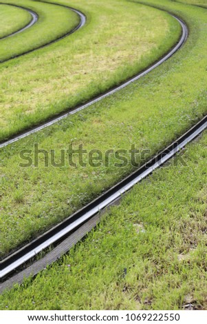 Close up outdoor view of tramway curved rails with green grass. Unban picture of parallel rails in large lawns. Abstract image of transportation by train and tram. Geometric shapes on the ground.