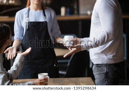 Close up outraged customers arguing with waitress in coffeehouse, bad service concept, unhappy angry man and woman displeased by drinks poor quality, talking, conflicting with cafe worker