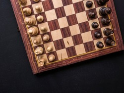 close up overhead chess board with pieces on black surface