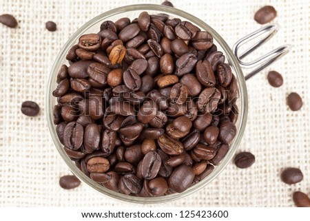 Close-up overhead shot of a pile coffee beans in coffee mug.