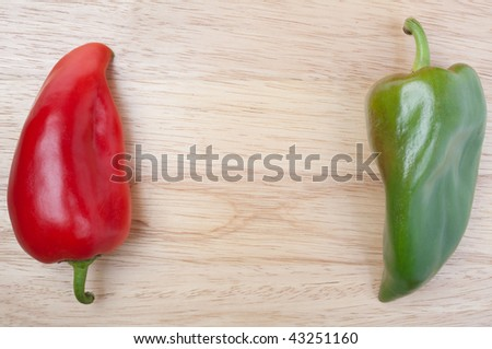 Close up overhead shot of red and green bell pepper on wooden board with empty space for your text