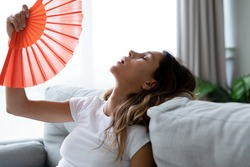 Close up overheated woman waving paper fan, breathing air, leaning back on couch alone, exhausted sick young female feeling unwell, suffering from heating, fever or hot summer weather at home