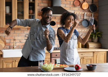 Close up overjoyed African American couple singing into kitchenware, having fun, dancing, listening to music in kitchen, cooking salad, excited wife and husband holding whisk and ladle a microphone Foto stock ©