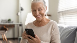 Close up overjoyed mature woman using phone, sitting on couch, browsing smartphone apps, looking at screen, senior female chatting with relatives online, shopping, having fun with mobile device