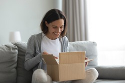 Close up overjoyed smiling young woman opening cardboard box with awaited parcel, sitting on couch at home, satisfied client received online store order, good quick delivery service concept